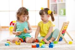 使用与积木一起的孩子 幼儿园和幼儿园孩子的教育玩具 小女孩修造 免版税库存图片