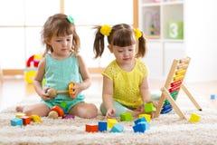 使用与积木一起的孩子 幼儿园和幼儿园孩子的教育玩具 小女孩在h的修造玩具 库存照片