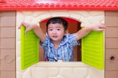 使用与窗口玩具房子的愉快的亚裔儿童男孩在操场 库存照片