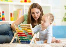 使用与算盘的孩子和母亲 库存图片