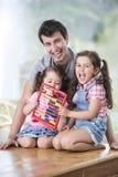 使用与算盘的愉快的父亲和女儿画象在房子里 免版税图库摄影