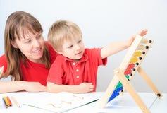 使用与算盘的母亲和儿子 免版税库存照片
