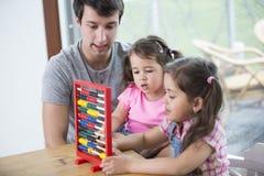 使用与算盘的父亲和女儿在房子里 免版税库存照片
