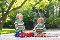 使用与红色校车的两个男朋友 免版税库存图片