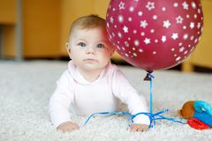 使用与红色气球,爬行的逗人喜爱的婴孩,劫掠 图库摄影