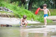 使用与纸小船的两个弟弟由一条河在温暖和晴朗的夏日 库存图片