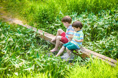 使用与纸小船的两个弟弟由一条河在温暖和晴朗的夏日 图库摄影