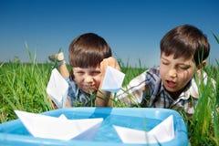 使用与纸小船的孩子 库存照片