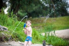 使用与纸小船的弟弟由一条河在温暖和晴朗的夏日 图库摄影