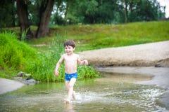 使用与纸小船的弟弟由一条河在温暖和晴朗的夏日 免版税图库摄影
