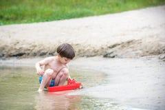 使用与纸小船的弟弟由一条河在温暖和晴朗的夏日 免版税库存图片