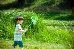 使用与纸小船的弟弟由一条河在温暖和晴朗的夏日 免版税库存照片
