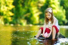 使用与纸小船的逗人喜爱的小女孩 免版税库存图片