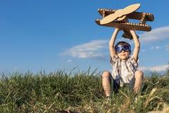 使用与纸板玩具飞机的小男孩在公园在Th 库存照片