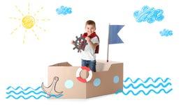 使用与纸板船的逗人喜爱的小男孩 库存照片