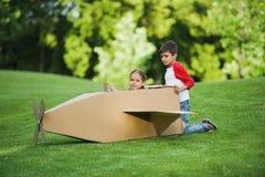使用与纸板飞机的小孩在绿色公园 图库摄影