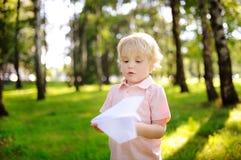 使用与纸飞机的逗人喜爱的小孩男孩在夏天公园 库存照片