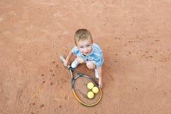 使用与网球拍和球的小男孩在网球场 在视图之上 免版税库存照片