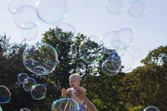 使用与肥皂泡的愉快的孩子反对蓝天 免版税库存照片