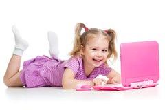 使用与膝上型计算机玩具的儿童女孩 免版税图库摄影