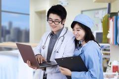 使用与膝上型计算机的两位医生在医院 库存照片