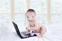 使用与膝上型计算机的婴孩 库存图片