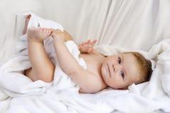 使用与自己的脚的逗人喜爱的矮小的婴孩在洗浴以后 在白色毛巾包裹的可爱的美丽的女孩 免版税库存照片