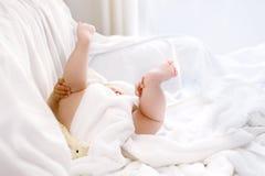 使用与自己的脚的逗人喜爱的矮小的婴孩在洗浴以后 在白色毛巾包裹的可爱的美丽的女孩 图库摄影