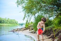 使用与船玩具的男婴海上 儿童os在度假在海滩的夏天在度假 库存照片