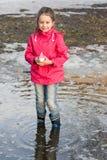 使用与船的雨靴的愉快的小女孩在春天站立在水中的小河 库存照片