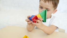 使用与色的块的儿童男孩,在慢动作 照相机从儿童` s面孔移动向玩具,在慢 股票视频