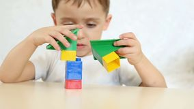 使用与色的块的儿童男孩,在慢动作 照相机从儿童` s面孔移动向玩具 影视素材