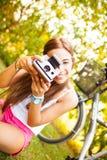 使用与葡萄酒照相机的美丽的少妇 免版税库存图片