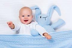 使用与蓝色的男婴编织了兔宝宝玩具 免版税图库摄影