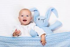 使用与蓝色的男婴编织了兔宝宝玩具 图库摄影