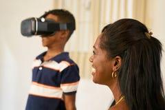 使用与虚拟现实风镜VR头的愉快的黑家庭 库存照片