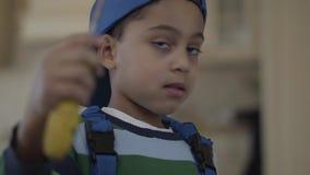 使用与螺丝刀的蓝色制服的假装逗人喜爱的矮小的非裔美国人的男孩他是修理匠 孩子介入了 影视素材