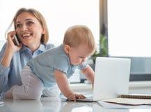 使用与计算机的感兴趣的孩子在妈妈附近 免版税库存照片