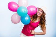 使用与许多五颜六色的气球的妇女 免版税库存照片