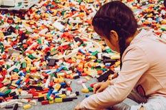 使用与许多塑料修造的砖零件的女孩 免版税库存图片