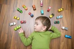 使用与许多的小白种人孩子室内玩具汽车 穿绿色衬衣的孩子男孩 愉快学龄前有乐趣在家或nu 免版税库存图片