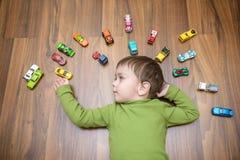 使用与许多的小白种人孩子室内玩具汽车 穿绿色衬衣的孩子男孩 愉快学龄前有乐趣在家或nu 免版税图库摄影