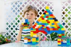 使用与许多的小白肤金发的儿童和孩子男孩五颜六色的塑料块 免版税图库摄影