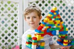 使用与许多的小白肤金发的儿童和孩子男孩五颜六色的塑料块 免版税库存图片