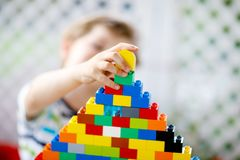 使用与许多的小白肤金发的儿童和孩子男孩五颜六色的塑料块 免版税库存照片