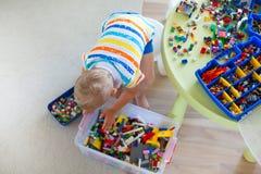 使用与许多的小白肤金发的孩子男孩五颜六色的塑料块 免版税库存图片