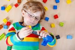 使用与许多的小白肤金发的孩子男孩五颜六色的塑料块 库存图片