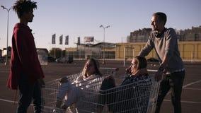 使用与购物车的不同种族的青年人 S 站立在与他们的购物的corts附近的男性朋友 影视素材