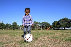 使用与足球的日本男孩 免版税库存图片