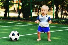 使用与足球的蓝色短裤的小男孩在运动场 一致的身分的白肤金发的孩子在与球的橄榄球场 库存图片
